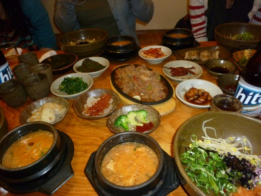 You can see bibimbap off to the right of the picture.  It's a very popular Korean meal.  Usually consists of rice, vegetables, and a little red pepper sauce.  The soup is kimchichigae.  It has vegetables and tofu in it.  It can be pretty spicy.