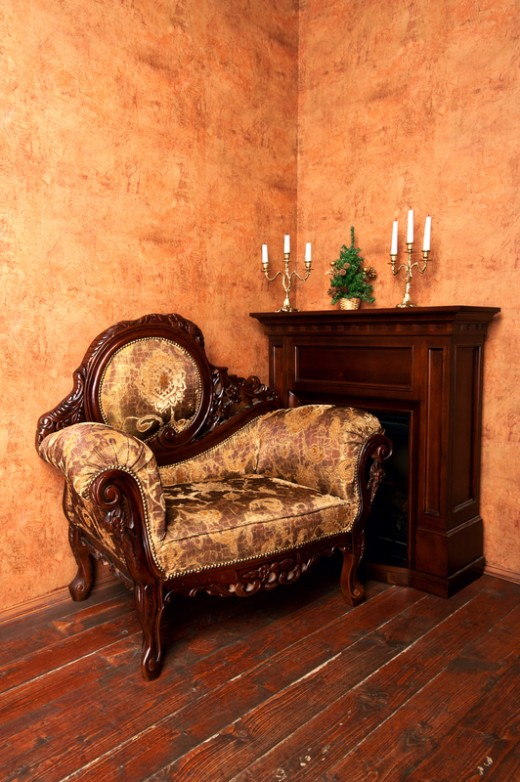 Old-fashioned interior with luxury armchair, fireplace, candelabras and small Christmas tree on ocher wallpaper background