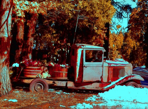 a rusted old truck with autumn pumpkins is an unusual autumn photo, made more interesting by the contrast of the snow..