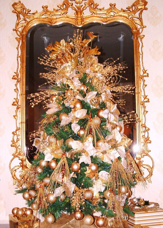 Elegant gold themed tree was displayed on a mahogany table with guilded mirror behind it.