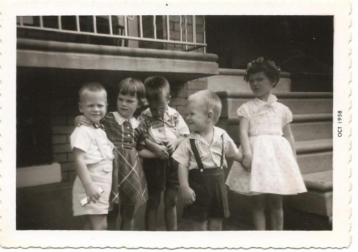"""That's me on the far right, then my two brothers, my cousin Diane, and my cousin Frankie. The row house porch appears just above our heads. Behind Frankie is the """"cellar window"""" where coal was delivered to heat our house."""
