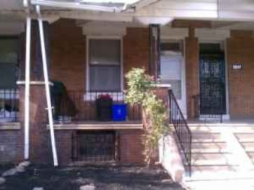 Row house with porch, steps are shared with house next door. Cellar window for easy access to deliver coal.