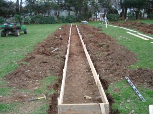 PREPARING FOR THE POURING OF CONCRETE FOOTINGS FOR CEMETERY MONUMENTS