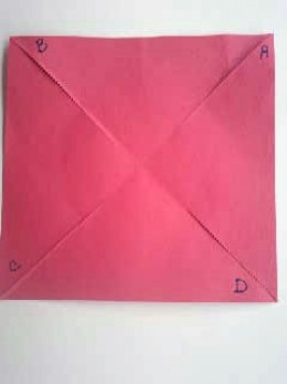 Red construction paper square is slit on four folds.
