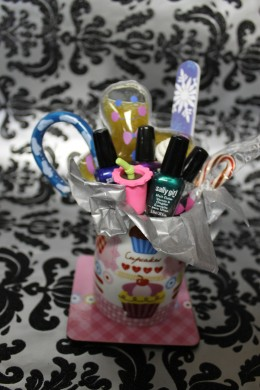 Small items arranged in mug with candy canes and a nail file arranged on the outside to hold everything together
