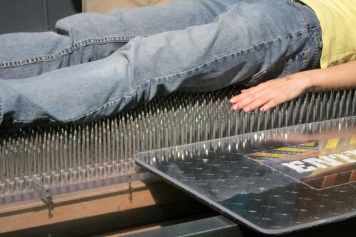 Lie on a bed of nails at WonderWorks