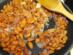 As the butter melts, the sugar starts melting too and clumping/adhering to the almonds.  Keep stirring.