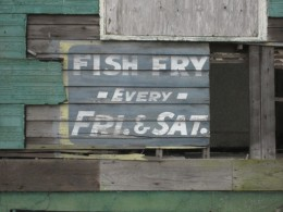 """Weathered old sign on side of building Uptown, advertising """"Fish Fry"""" held every Friday and Saturday."""