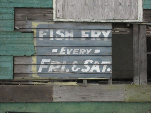 "Weathered old sign on side of building Uptown, advertising ""Fish Fry"" held every Friday and Saturday."