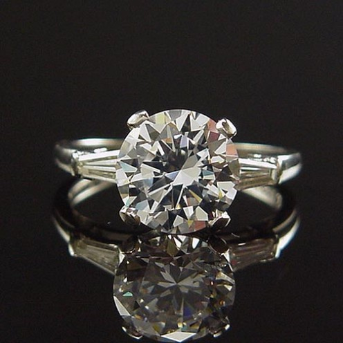 Exquisitely simple Art Deco engagement ring showcases the uncluttered yet aesthetically balanced lines of deco design.