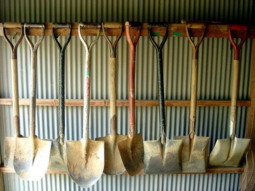A collection of dirty spades and shovels.
