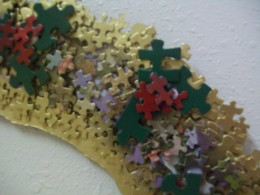 "a close up view,... note the use of three larger green pieces with three smaller red pieces to render the ""holly"" look"