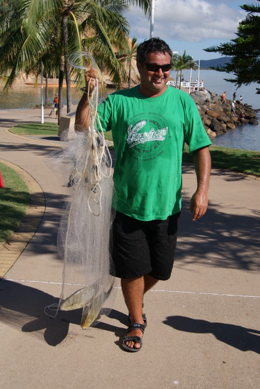 Catching fish with a throw net into the ocean at the Lagoon end of The Strand.