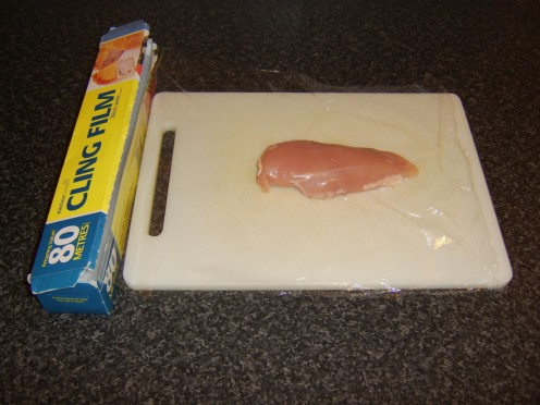 Chicken breast is wrapped in clingfilm