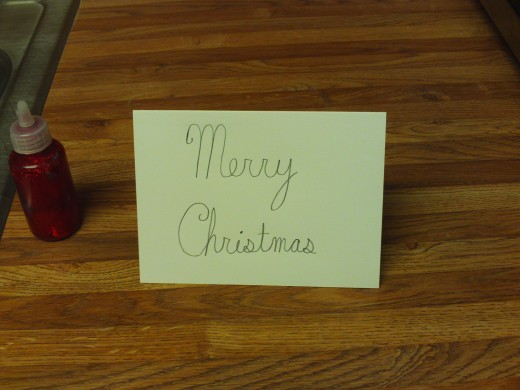 "Next, I folded my card in half, and had the red glitter glue ready to trace over ""Merry Christmas""."
