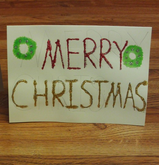 I used two green colored pencils to draw a wreath on each side of the card.
