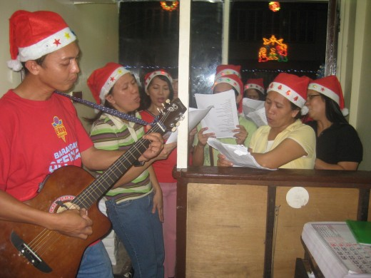 Travel Man on guitar and the rest of Don Galo Coop ladies practicing before the caroling (Photo by Travel Man)