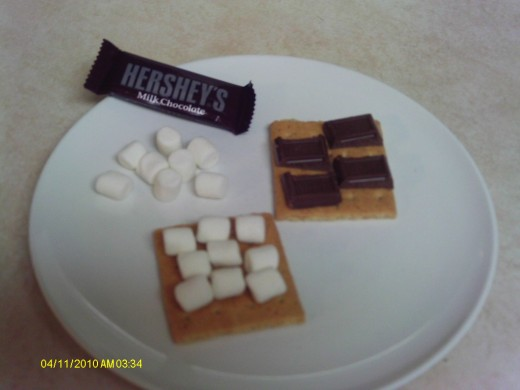 Place the ingredients on the crackers: marshmallows and chocolate hershey bar