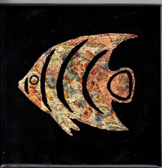 Gilded fish on black ceramic tile