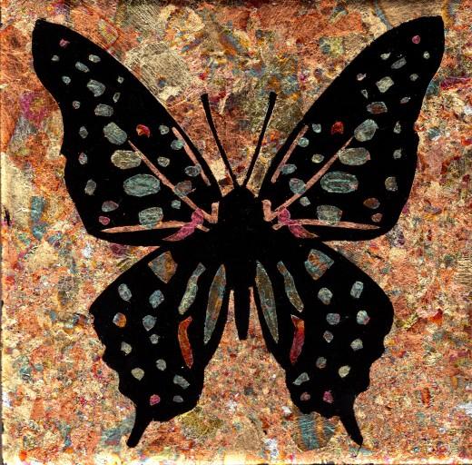 Reverse gilded butterfly on black ceramic tile
