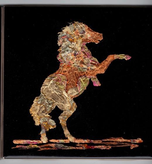 Gilded horse on black ceramic tile