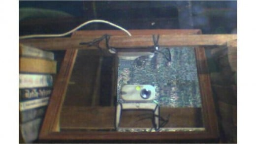 view of the same webcam through two mirrors: one mirror is below the webcam inclined at 45 degrees with another vertical mirror in the frontal direction of the  inclined mirror. Top webcam is vertical mirror's view,  lower webcam is inclined mirror's