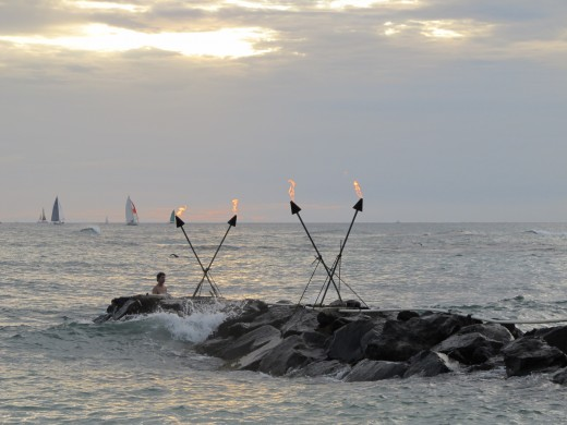 Lighting the torches as the sun sets. Outrigger Canoe Club