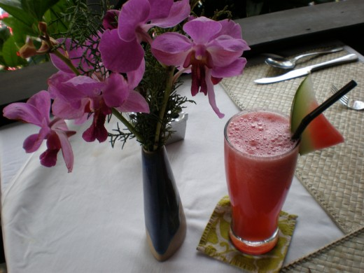 The tropical equivalent of a coffee break, a fresh watermelon juice and some smile provoking orchids; Ubud, Bali, Indonesia.