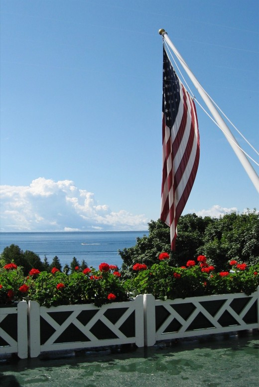 Geraniums & U.S. flag on the porch of the Grand Hotel