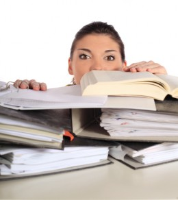 Business woman being swamped with a pile of papers and binders.