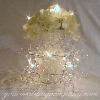 Cream hydrangea centerpiece accented with a 10-mini light set and a crystal garland.
