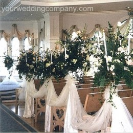Pews draped with tulle fabric and white lights.