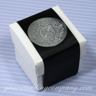 A 2-inch white glossy box filled with almonds and decorated with satin ribbon and a silver seal.