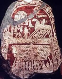 Gotland stone showing a ship under sail below Asgard, a memorial to a sea-going raider... A Viking!