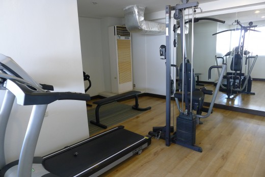 A tiny fitness center with a massive air conditioning unit.