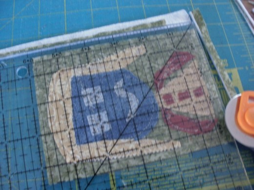 After you have attached the shapes by sewing them to the Timtex, it is time to add the backing and trim them up to the proper postcard size.