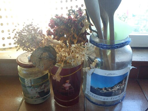 Things tend to look nicer in decorative glass jars.  A little yarn trim is wound around the top of the largest bottle.  I used postcards and rubber bands for a quick and easy look.  The one on the right is soaked, peeled and pasted.