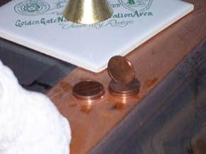 The most convincing photograph of spirit penny manipulation is this one that was taken from a home that I investigated in Oakley, California.  Not only had the penny stack moved into two stacks, but the top penny is standing on its edge on top of one