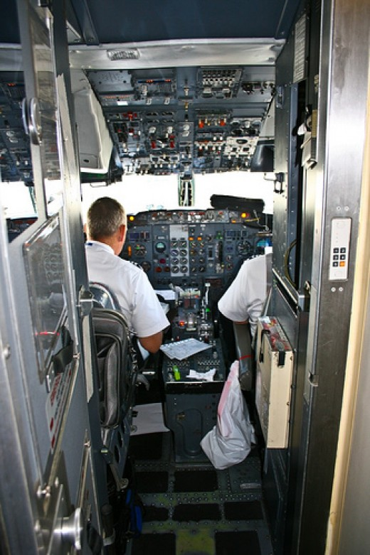 Pilots perform their airline jobs in the cockpit.