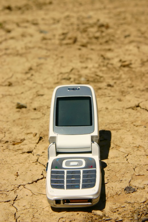 WHITE MOBILE PHONE IN A DRY RIVER BED by Startoucher White mobile cell phone in a dry, cracked river bed