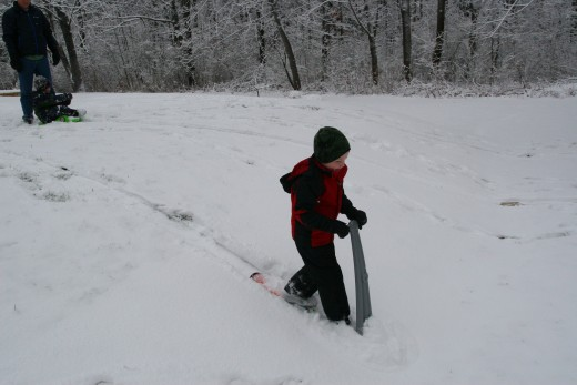 My six year old on his Pelican Snow Scooter. He is allowed to use it on gentle slopes, like this one in our backyard..