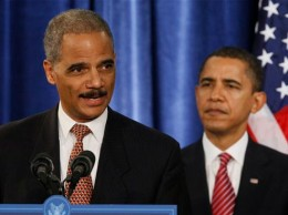 Attorney General Eric Holder at podium with Pres. Obama