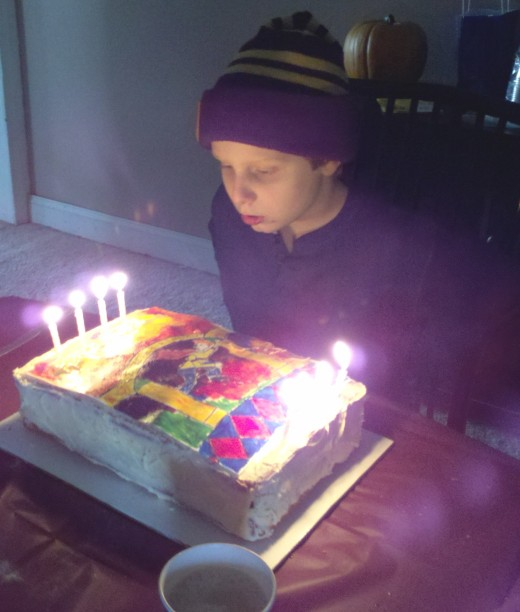 The birthday boy blows out the candles on his book cover inspired cake.