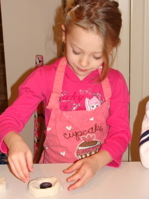Grace carefully cuts the hole into the biscuit.