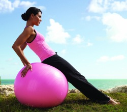 pretty woman in pink leaning on a pink balance ball - same color as cancer pink