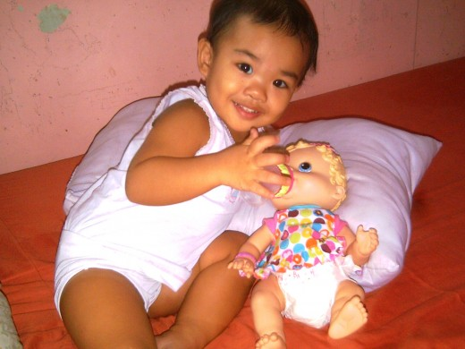 Baby Pauleen posing with her doll