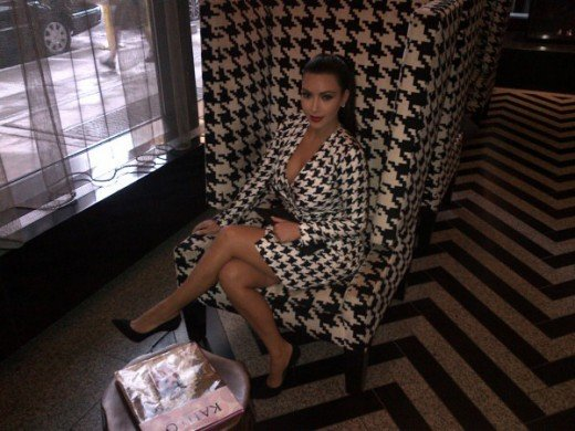 Kim Kardashian in a lovely plunging v-neck dress blends in with a wing back chair also in houndstooth at the Gansevoot Park Hotel in NY.
