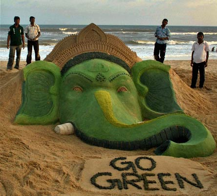 A sand sculpture depicting the face of Lord Ganesha and urging people to save the planet by using environment friendly measures.