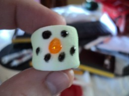 Use black gel frosting to make two eyes and a mouth on the small marshmallow.  Use orange frosting to make a carrot nose.