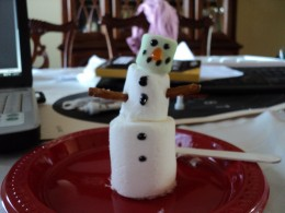 Take two small pretzel sticks and insert them on each side of the regular sized marshmallow to make the arms of the snowman.